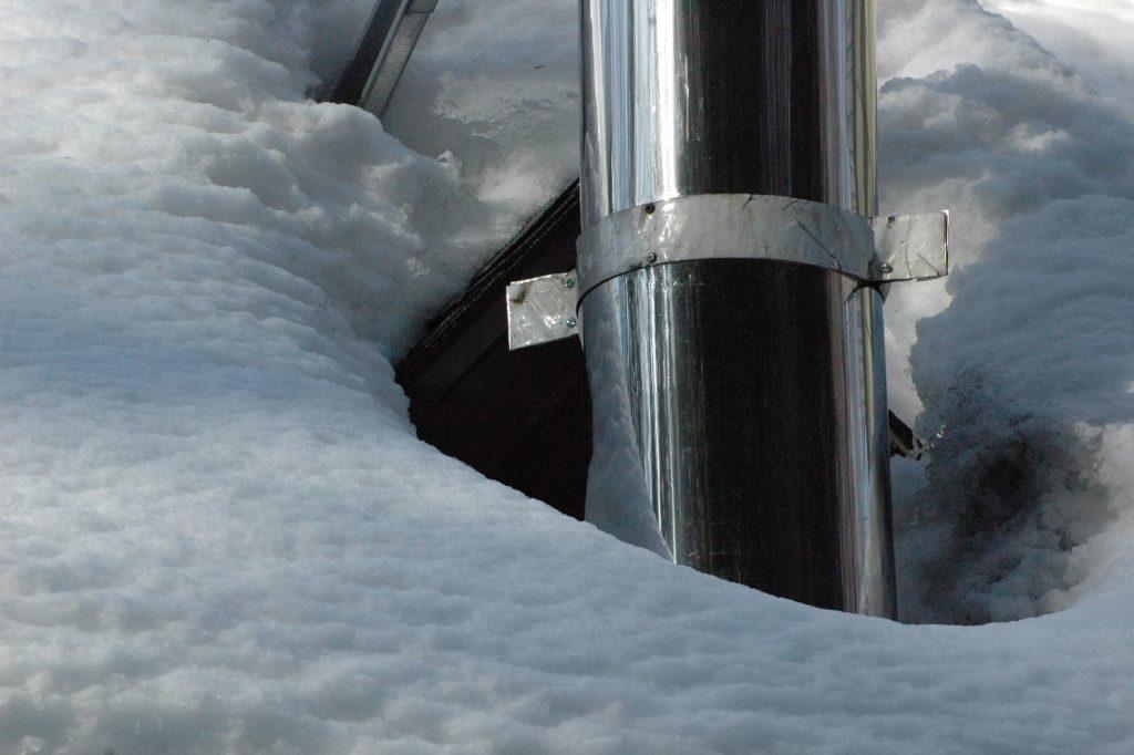 Photo BEBEXPERTS démontrant l'infiltration par la toiture par la neige  autour de la cheminée.